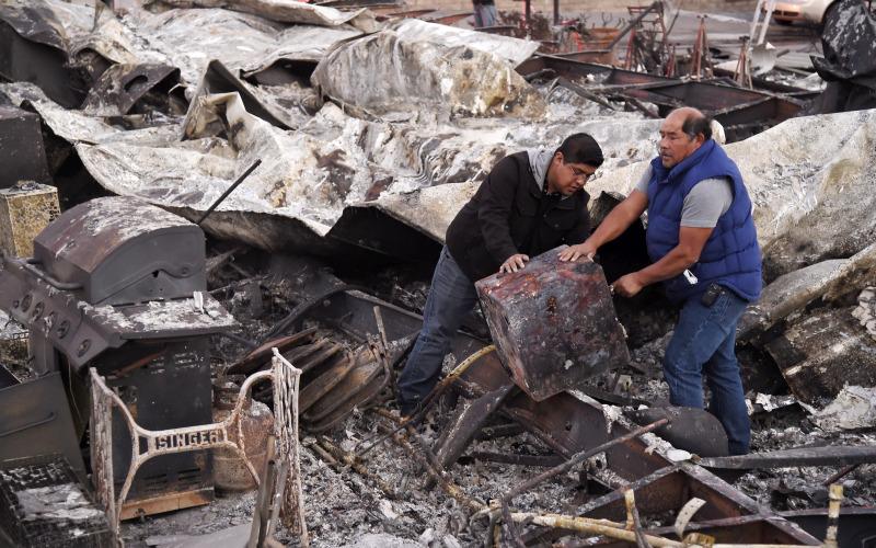 搜索人员继续在废墟和被烧毁的汽车中寻找失蹤人士。