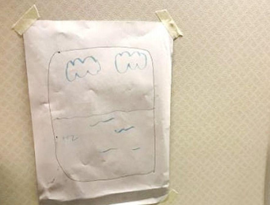 空中服务员将一张画上窗户、白云及海洋的纸张贴在该男乘客的位置旁边。网图