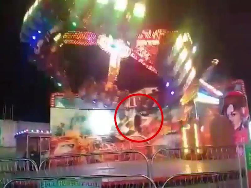 由于游乐园的设施故障,导致一名少女不仅悬空挂在旋转飞碟上。(网图)