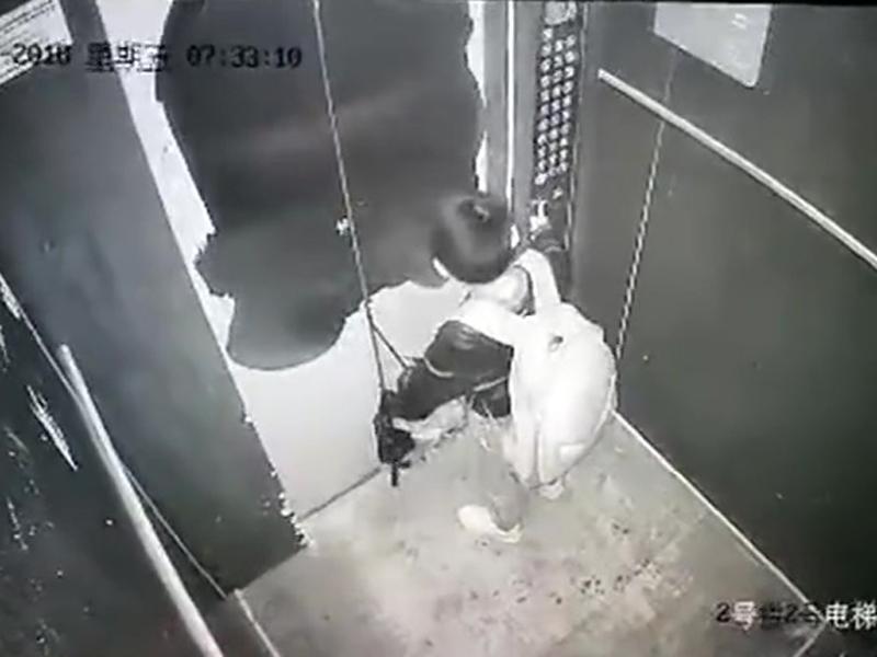 男童将雨伞柄卡住电梯门。(网图)