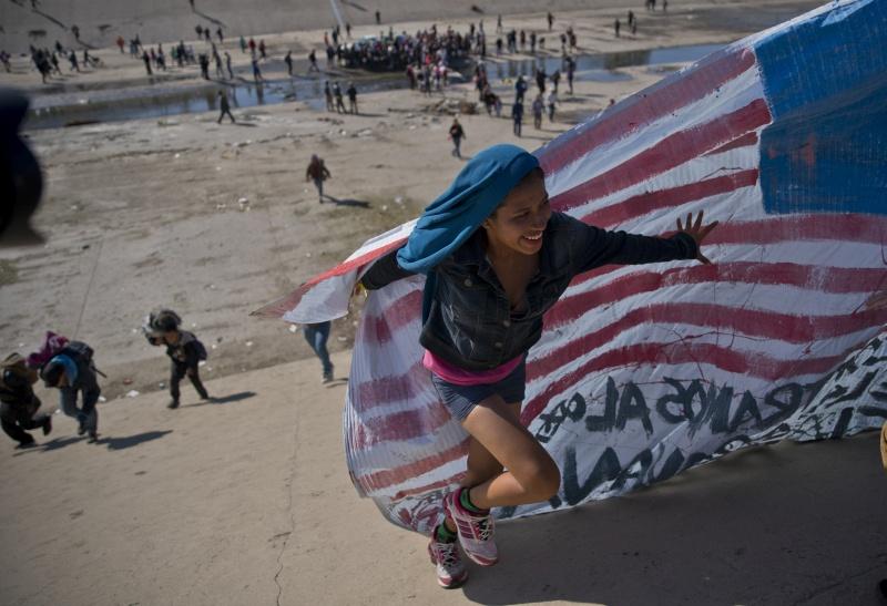 難民手持自行繪製的洪都拉斯和美國國旗,高叫「我們不是罪犯!我們是國際工人!」的口號。(網圖)
