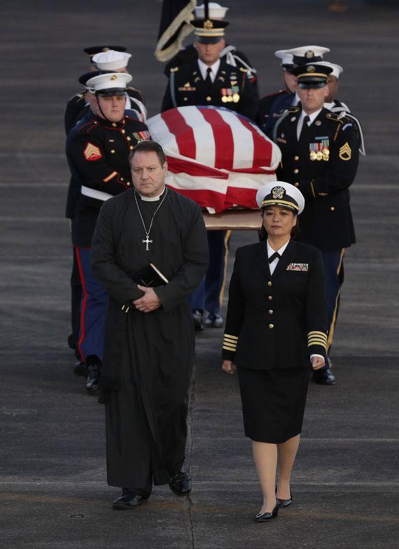 仪仗队把盖上国旗的灵柩抬出国家大教堂。