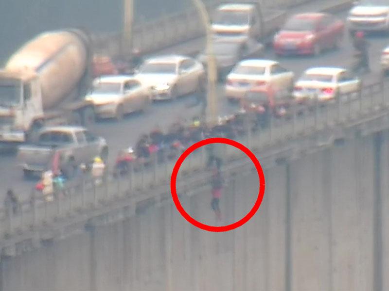 一名年輕女子翻過大橋安全護欄欲跳江輕生,被過路市民拉住。(網圖)