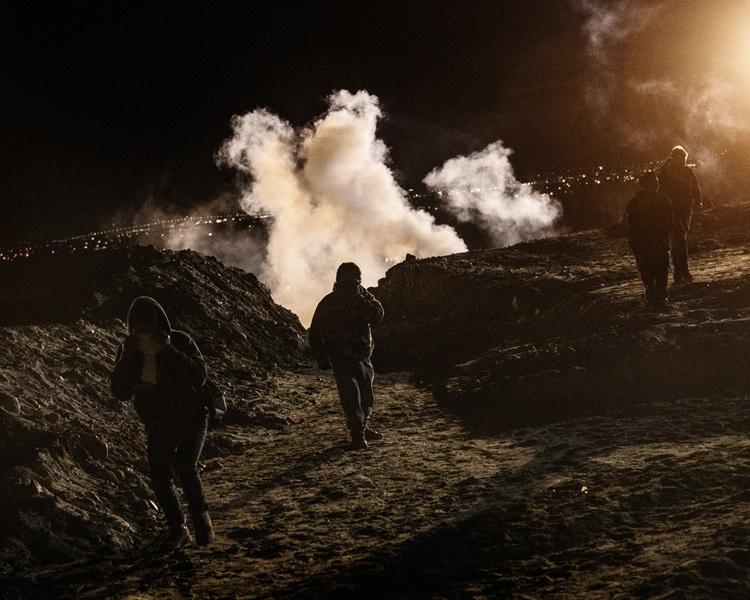 移民躲避催泪弹。AP