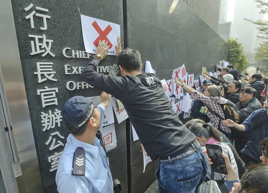 團體在特首辦外張貼標語,反對政府把長者綜援申請年齡下月起上調至65歲。陳浩元攝