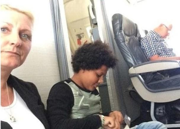 宝拉(左)和女儿被迫坐在机舱地板上。(网图)