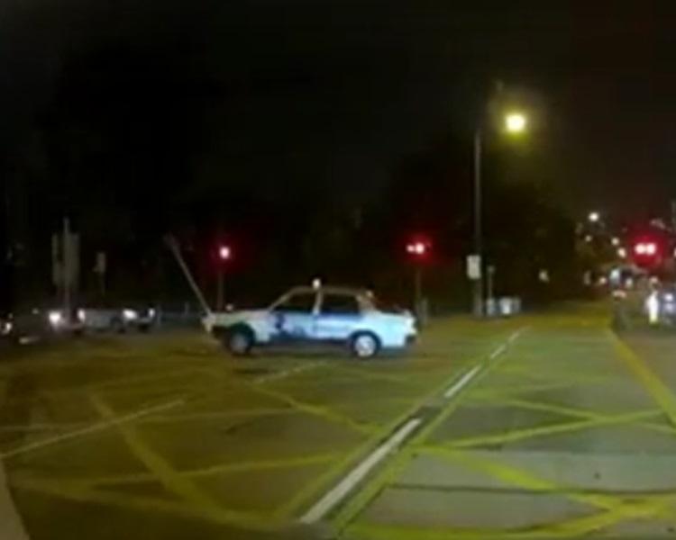 一辆红色的士撞到路中心的告示牌和安全岛灯箱。Linda Hui fb片段截图