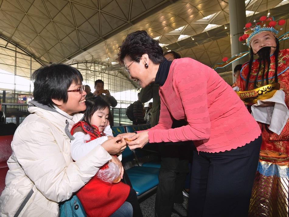 林鄭月娥在機場向市民及旅客拜年,並派朱古力及合照。新聞處