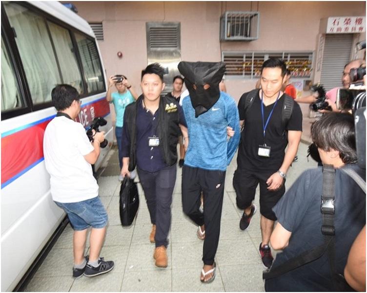 被告被警方蒙頭押上警車。資料圖片