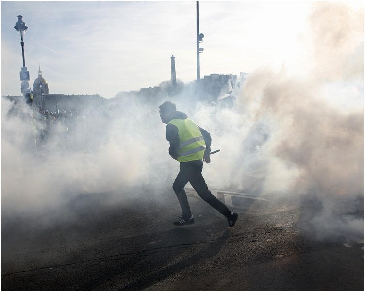 防暴警察施放催泪弹驱散群众。