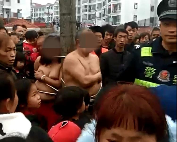 偷情男女被赤裸绑在树上。影片截图