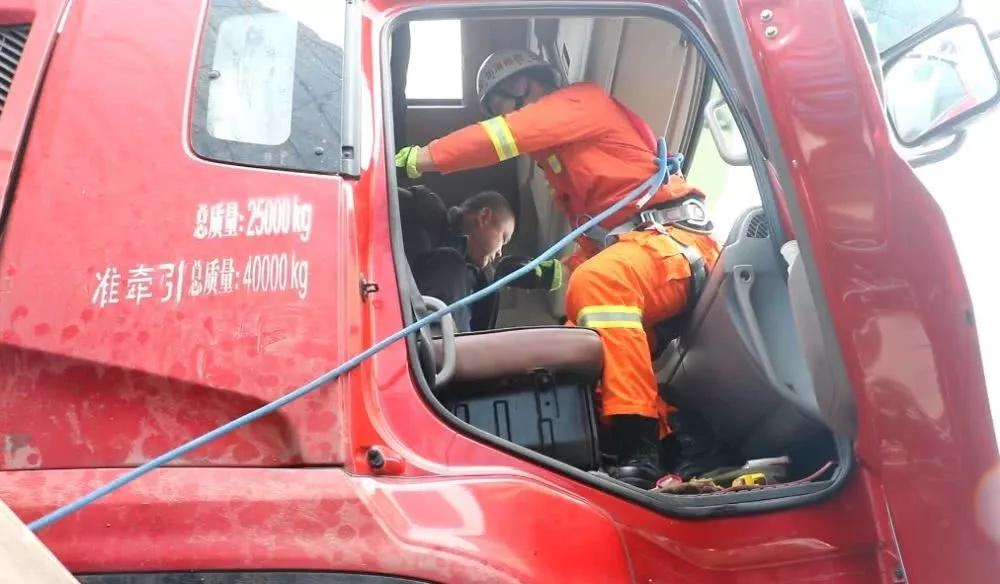 救援小组从右侧隙缝进入驾驶室内,对被困车内男子进行营救。