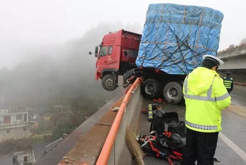 货车撞向护栏,车头悬挂在20米的高空。