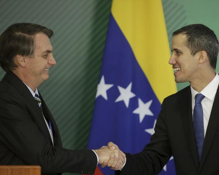 巴西总统Jair Bolsonaro(左)与瓜伊多握手。