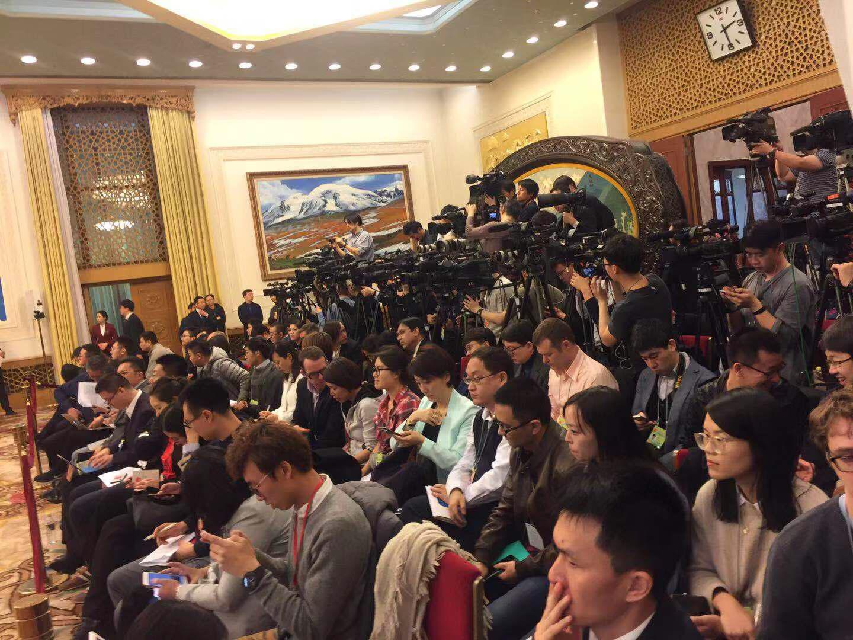 上百名记者集体进入新疆厅,瞬间已经座无虚席,不少人只能席地而坐。董秋伊摄