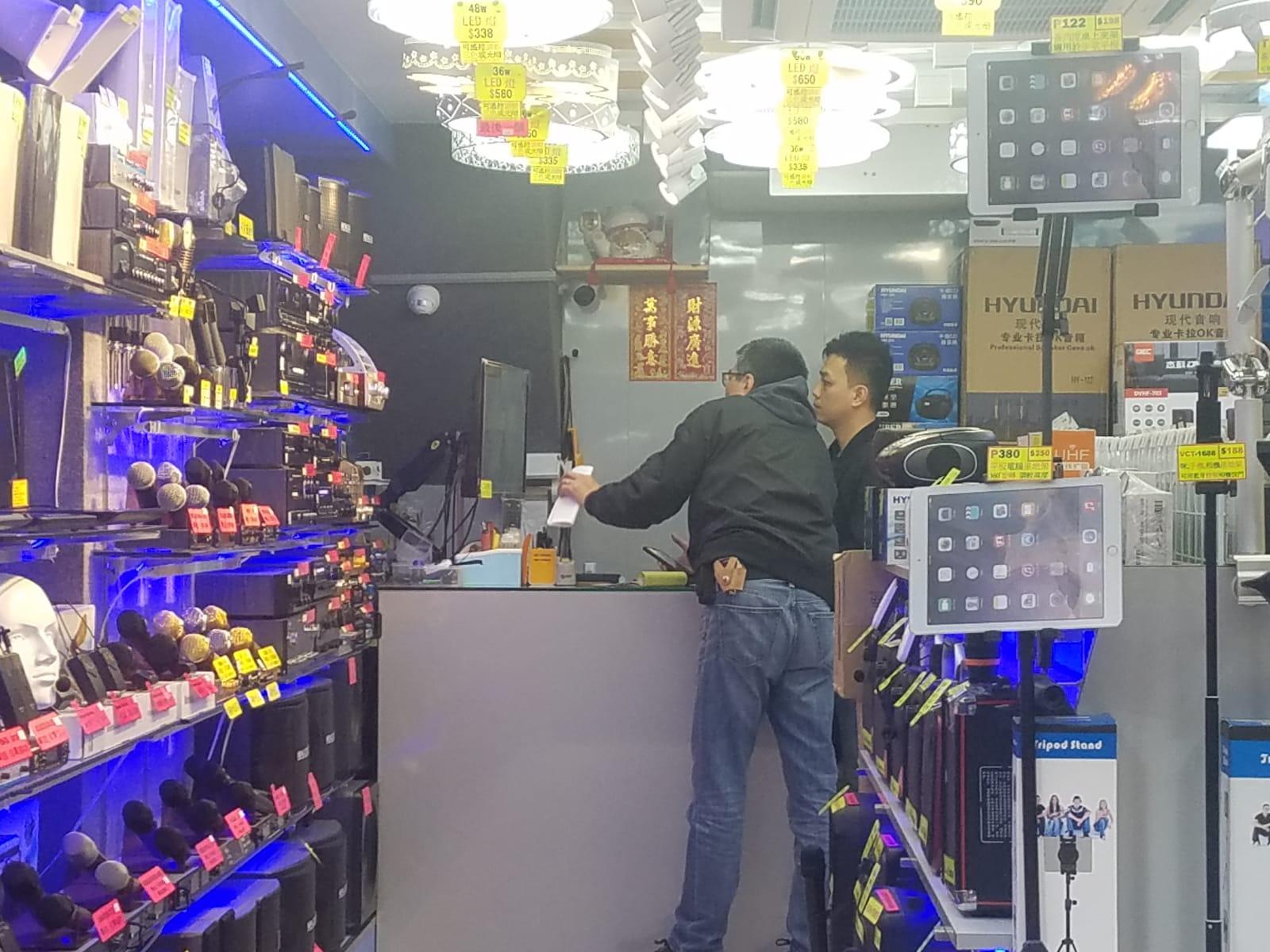 探員在案發現場附近查閱其他店鋪的閉路電視。