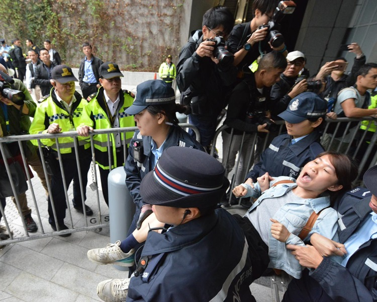 示威者被警方抬走。