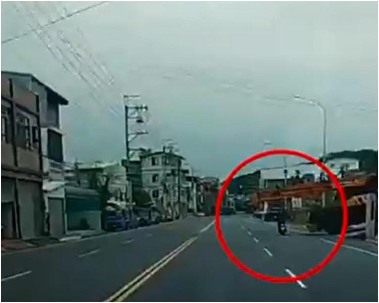 电单车从一辆大型起重机吊臂车下穿过时发生意外。网图