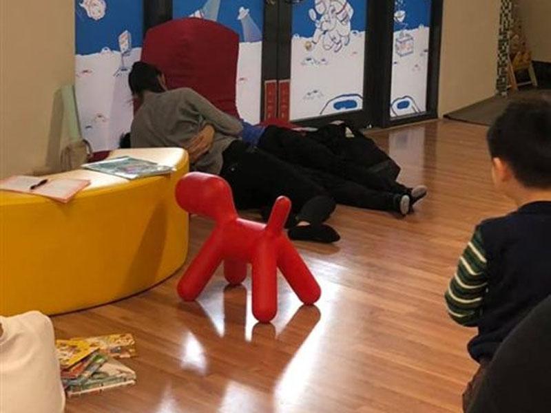 一對情侶在圖書館內摟抱糾纏,旁邊童看呆了。(網圖)