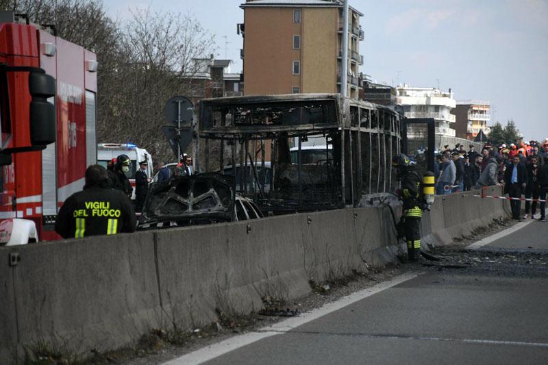 校巴烧剩焦黑的支架,消防员在车顶洒水降温。