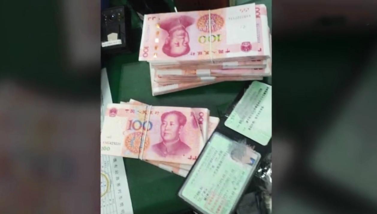 民警將手袋打開檢查,裡面有66800元人民幣。  影片截圖