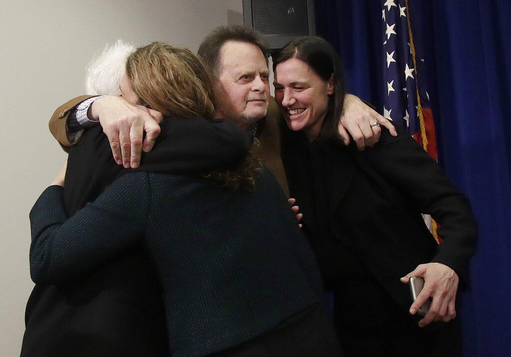 哈德曼在裁決宣布後,擁抱妻子和律師團隊成員。美聯社圖片