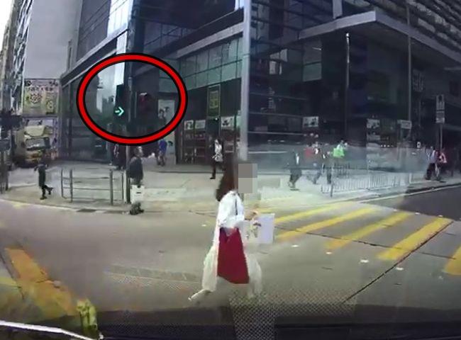 少女在红灯亮起期间,打斜横跨两条马路。影片截图