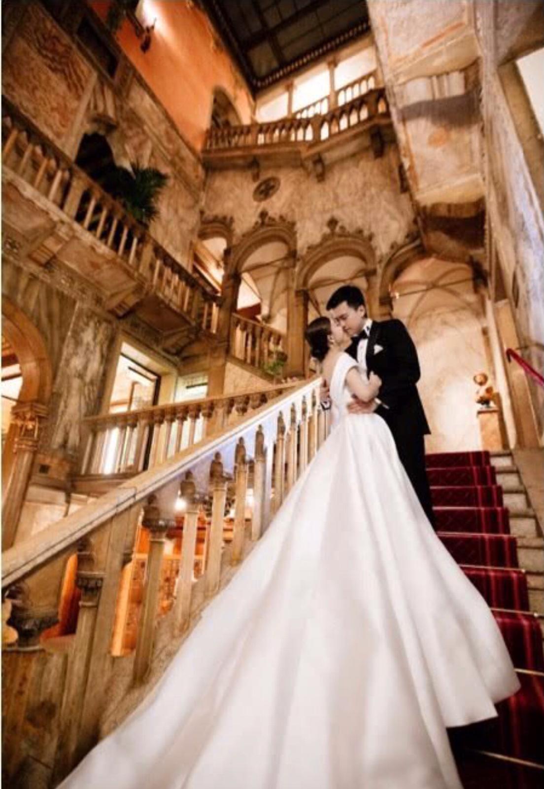 兩人站在古堡的樓梯上情深一吻。