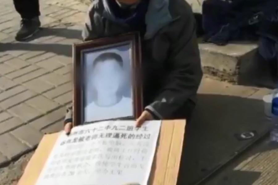 该学生家属带着孩子的遗照到学校大门前,要求校方给个交代。 网上图片