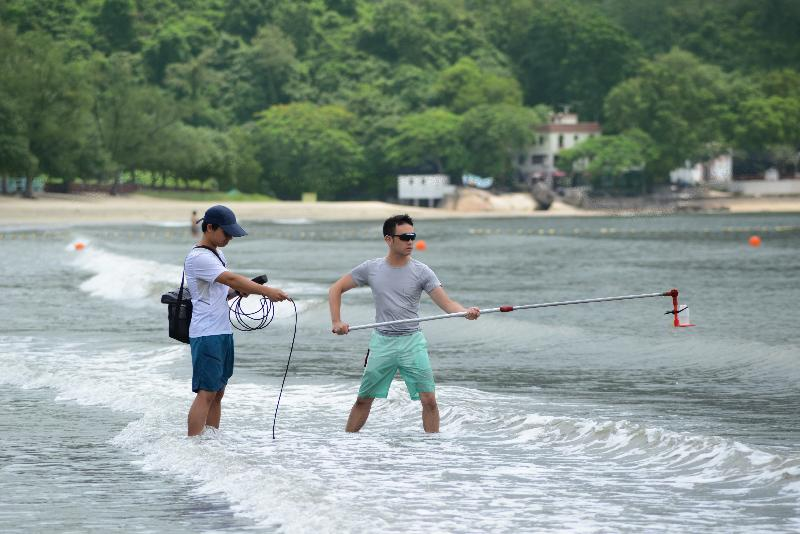 環境保護署人員在泳灘實地抽取海水樣本及量度現場數據。  政府新聞處圖片