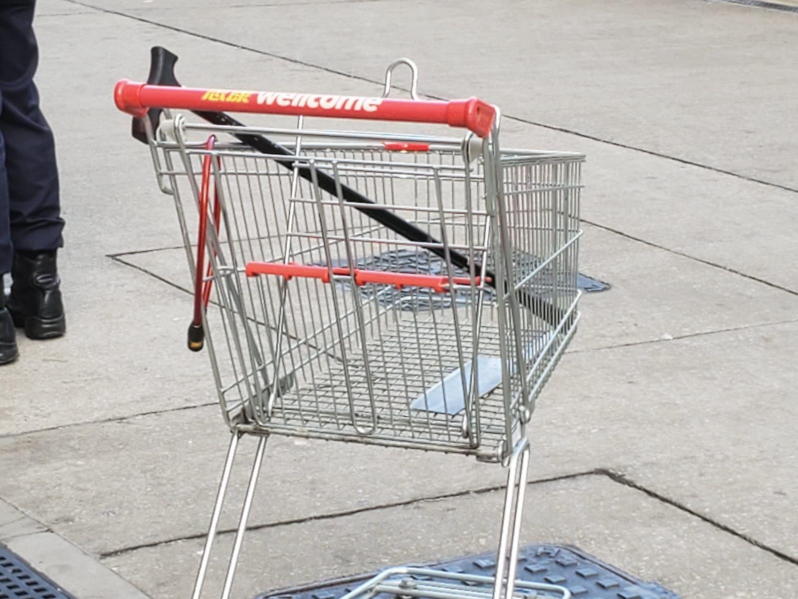 一輛超市手推車載着拐杖及菜刀