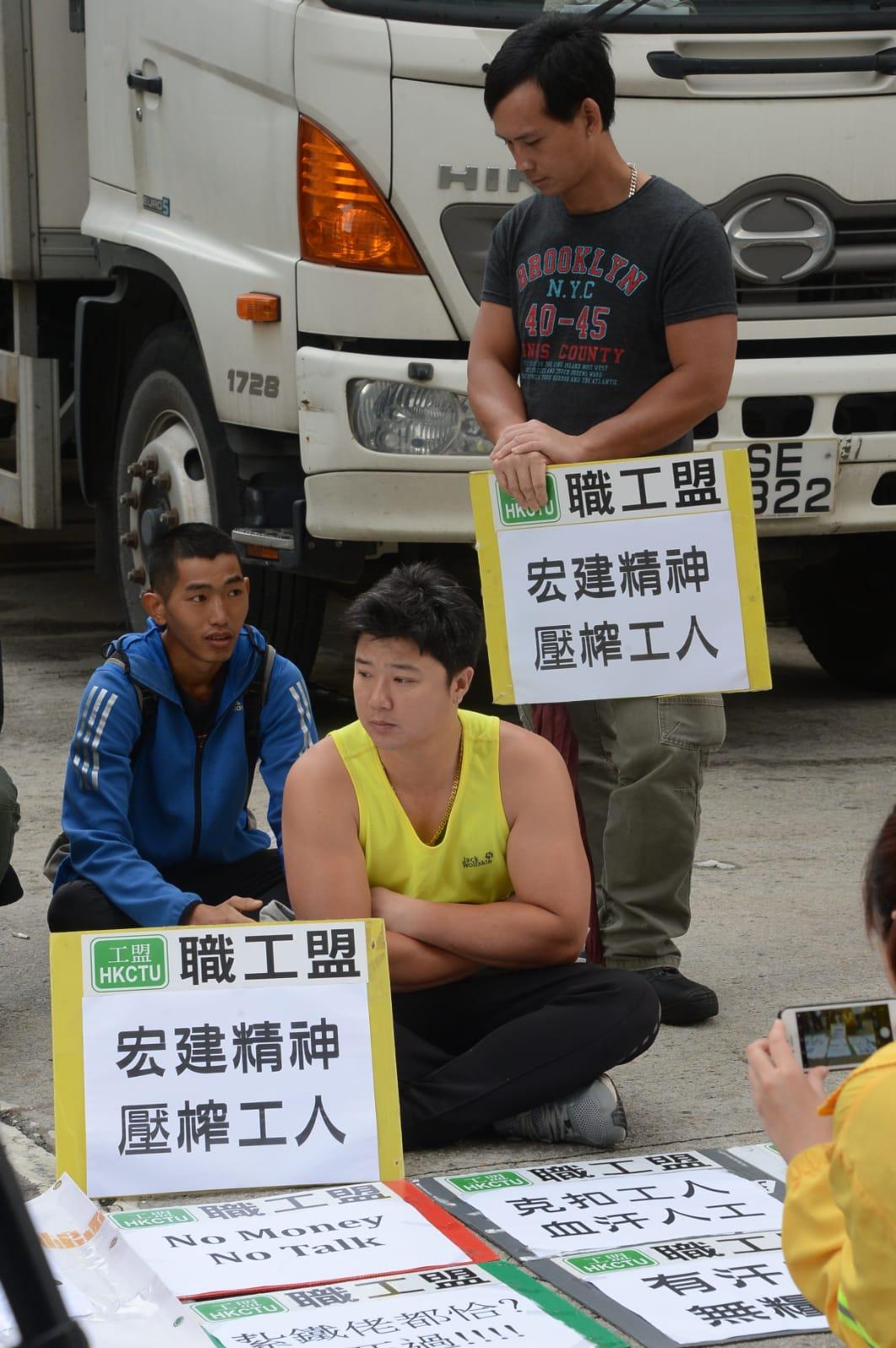 多名紮鐵工在地盤入口靜坐抗議。