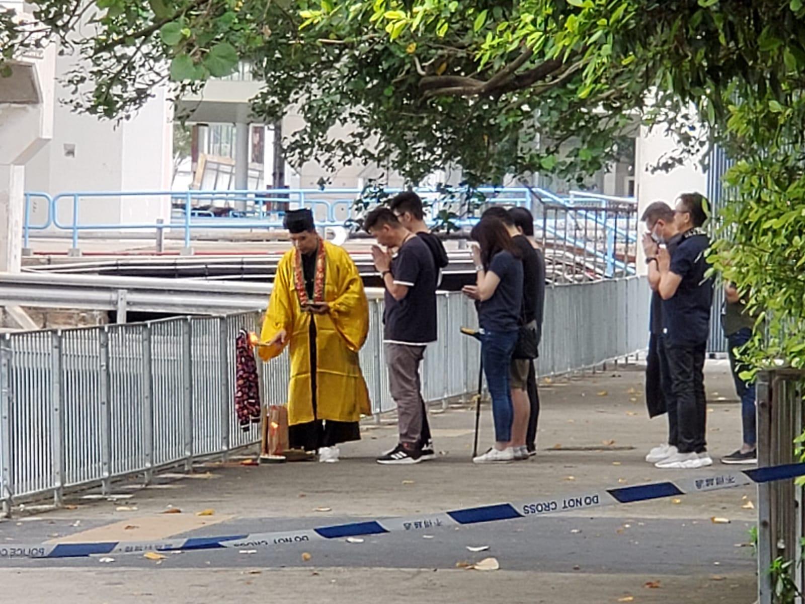 女事主親友一行近10人在觀塘碼頭海邊做法事。