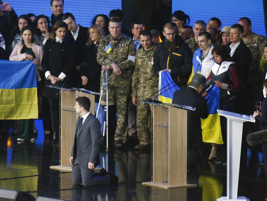 烏克蘭總統大選辯論會中,兩名候選人澤連斯基(左)與波羅申科一起向觀眾下跪。