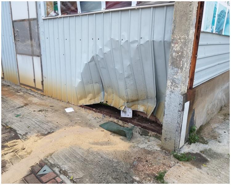 鐵騎士飛撞至鐵皮外牆,牆身凹陷。