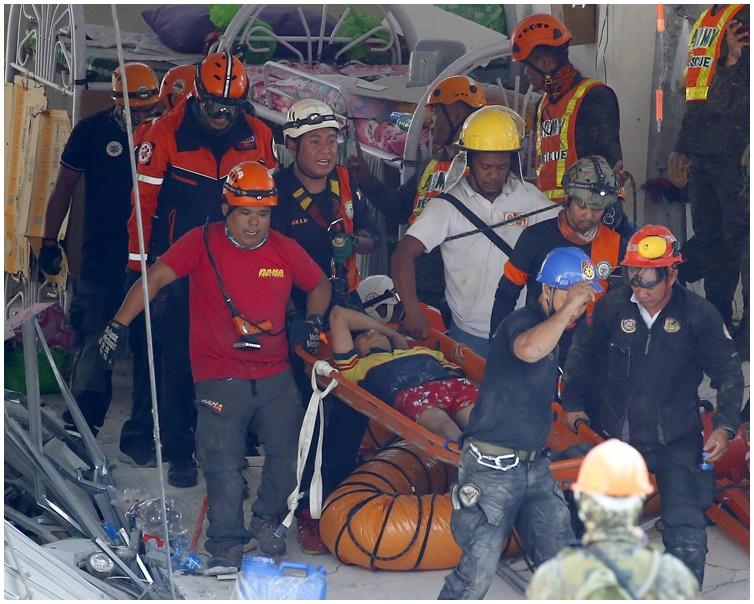 救援人員於瓦礫中救出3名生還者。AP
