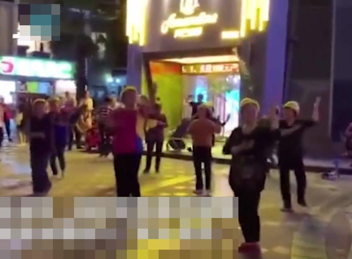 一群大媽為繼續在廣場上跳舞,竟不惜戴上安全帽。網圖