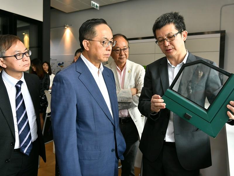 楊偉雄(左二)參觀一家建築節能產品公司的廠房。政府新聞署圖片