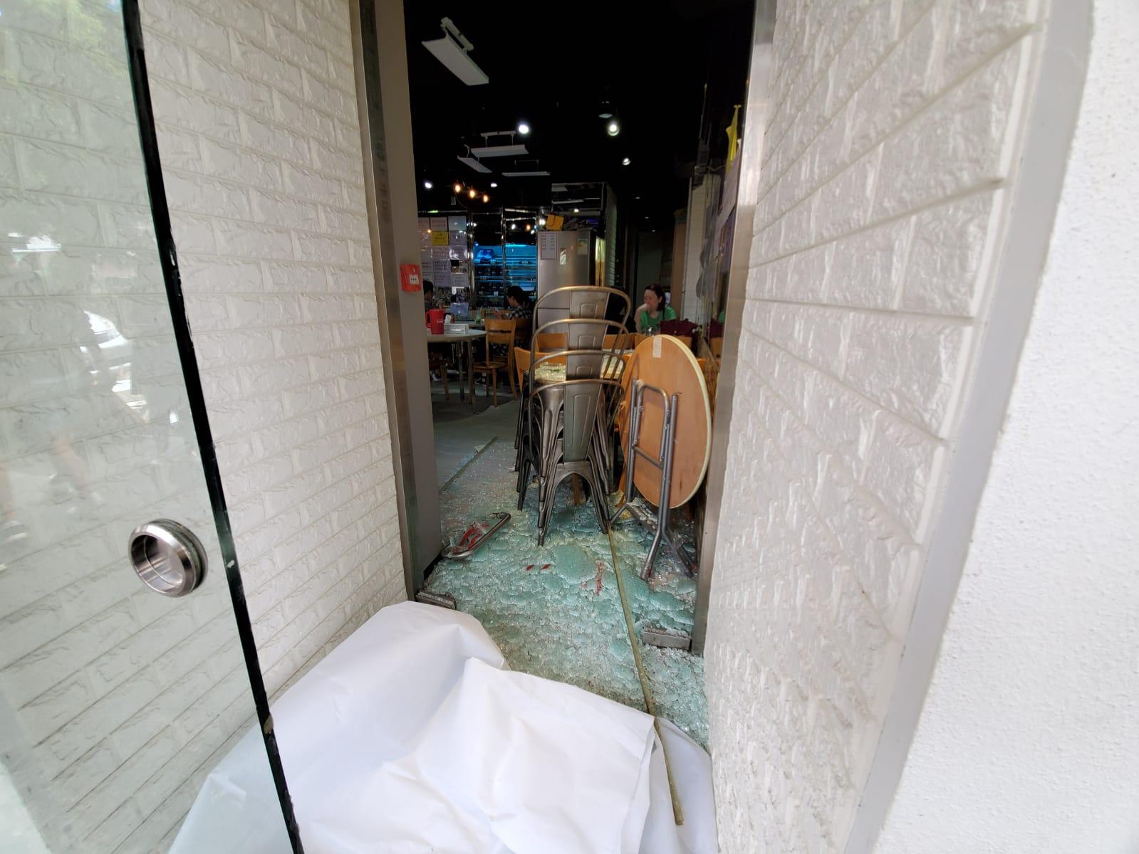 食店其中一隻玻璃門遭扑毀,碎片散落一地。 林思明攝