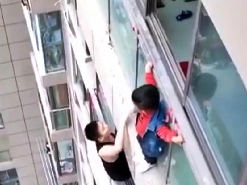 男孩14樓外牆大哭,鄰居爬到13樓窗外安撫孩子。(網圖)