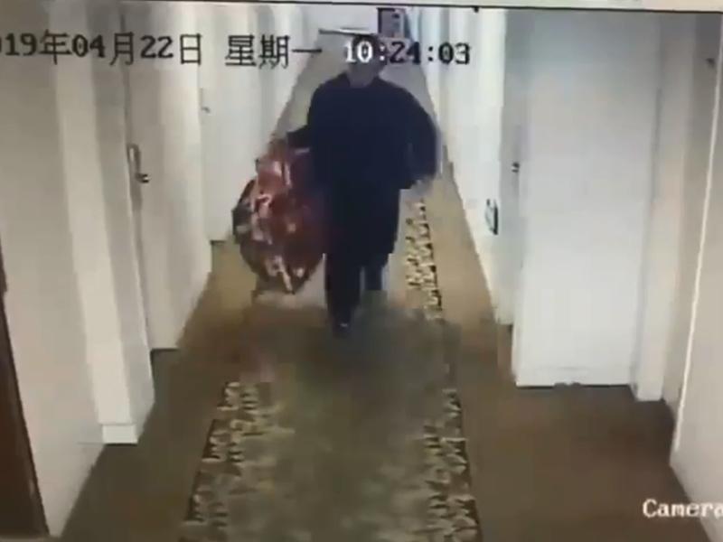 上海賓館男房客將電視機裝在布袋裏帶走。 影片截圖