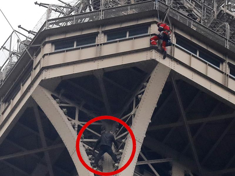 法国一名身穿黑色上衣的男子徒手爬上巴黎艾菲尔铁塔。