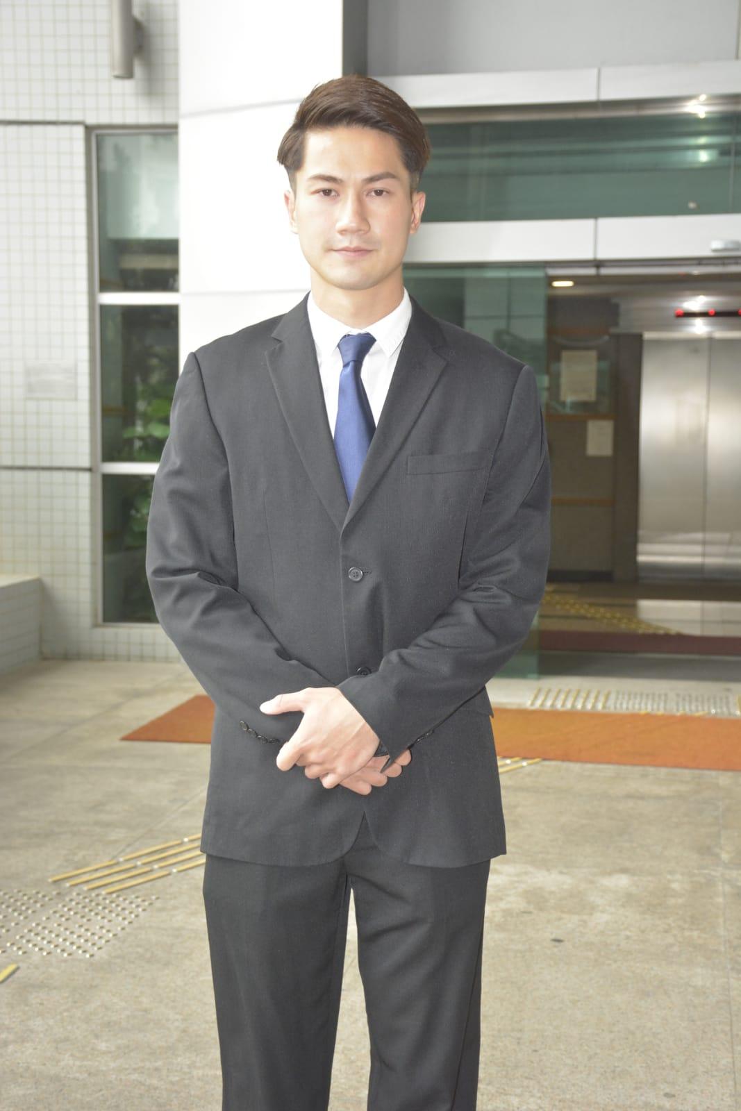 身穿黑色西裝配藍色領帶的郭子豪,在法院外企定定讓傳媒拍攝才展露微笑。