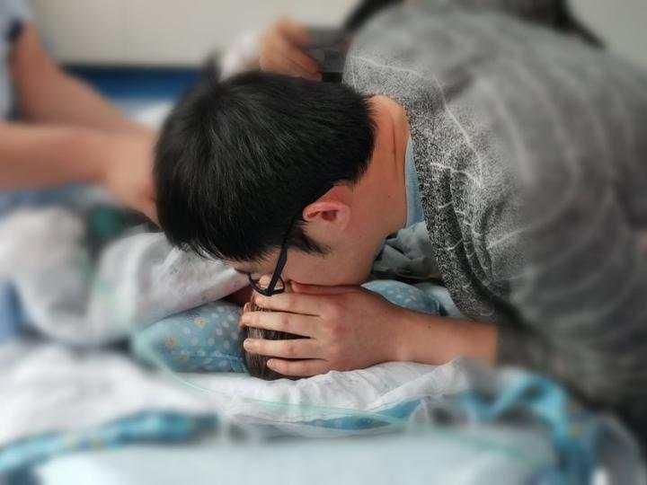 進手術室前,爸爸親吻小毛豆。網上圖片