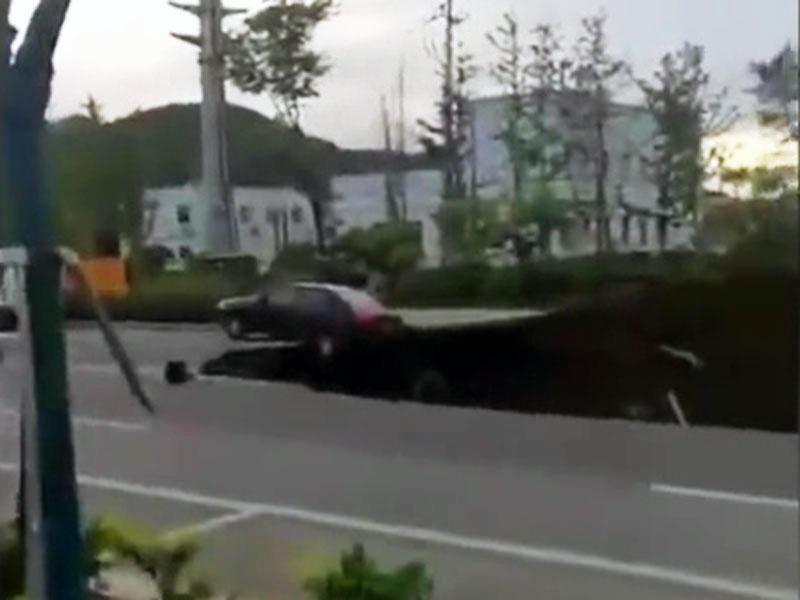 路面出現大面積塌陷,一輛汽車,停在塌陷坑邊緣。(網圖)
