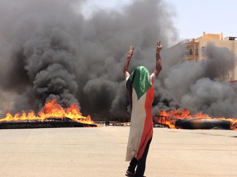 一名戴着苏丹国旗的示威者在燃烧的轮胎和碎片前摆出胜利手势。