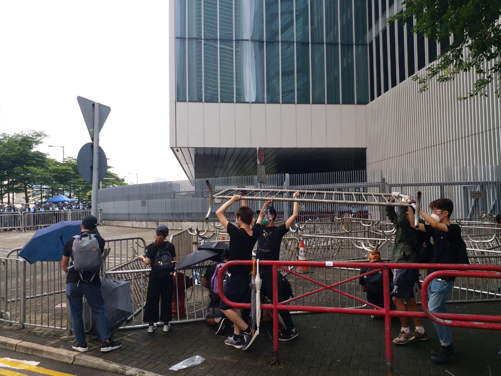 示威者拿起路旁的鐵架,放置在公路上阻塞立法會出入口。