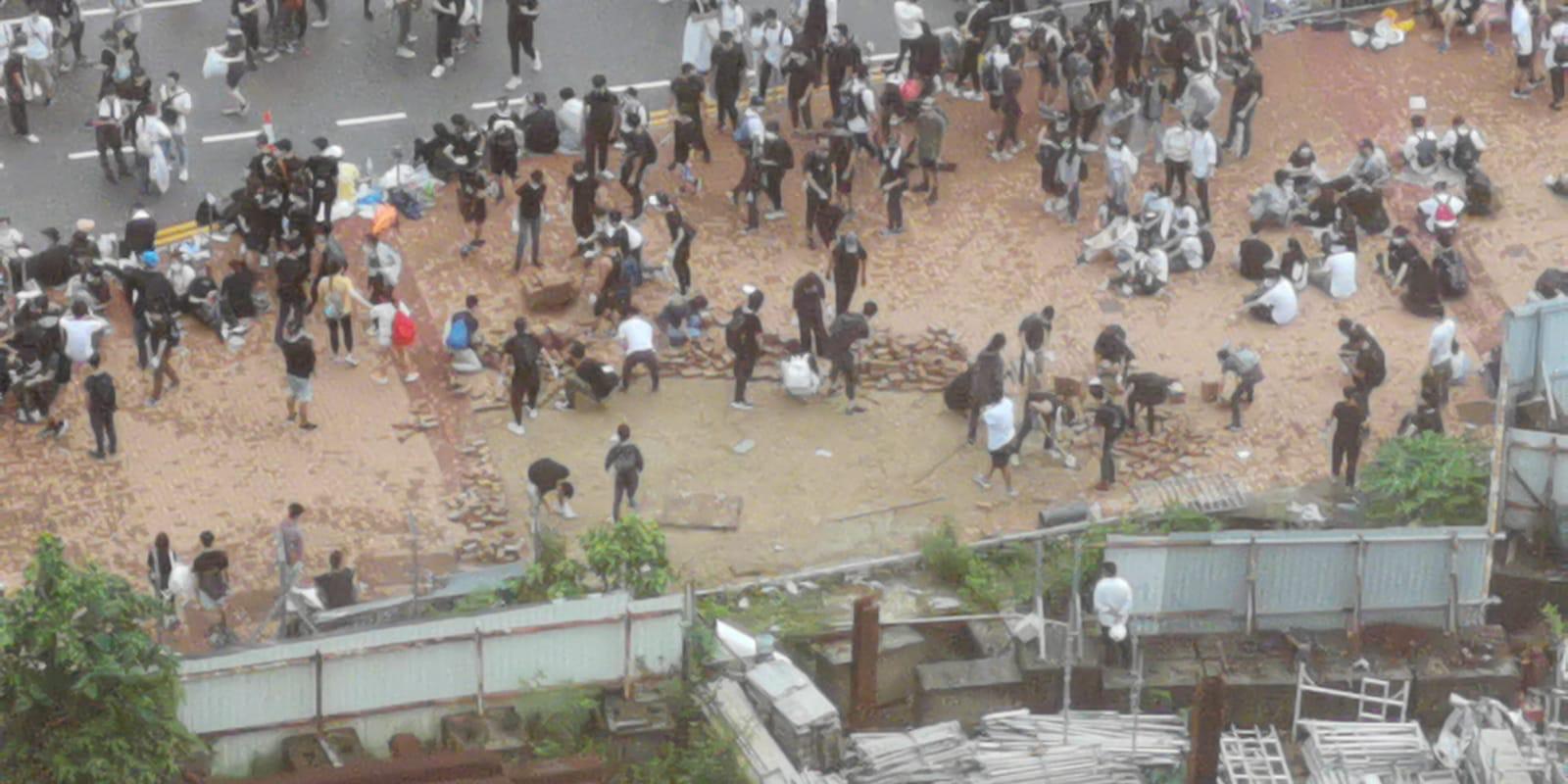 有示威者把地上磚頭掘起。