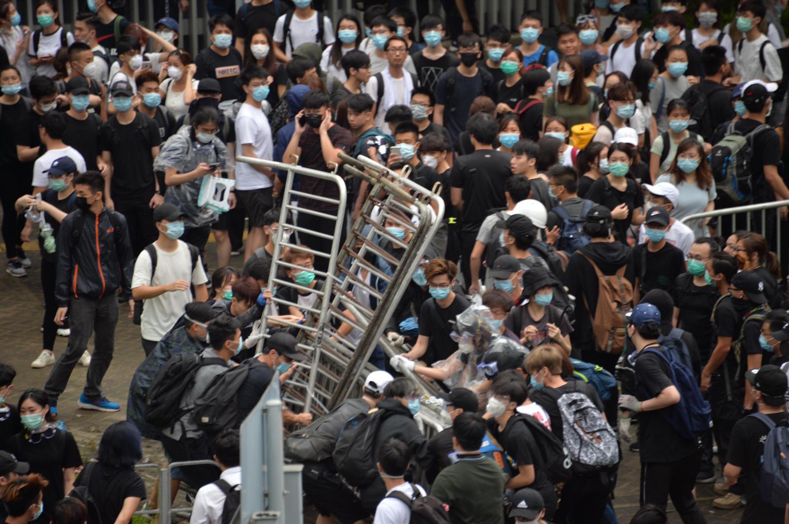 部分示威者身穿黑衣黑褲、戴上口罩及頭盔,架起鐵馬陣。