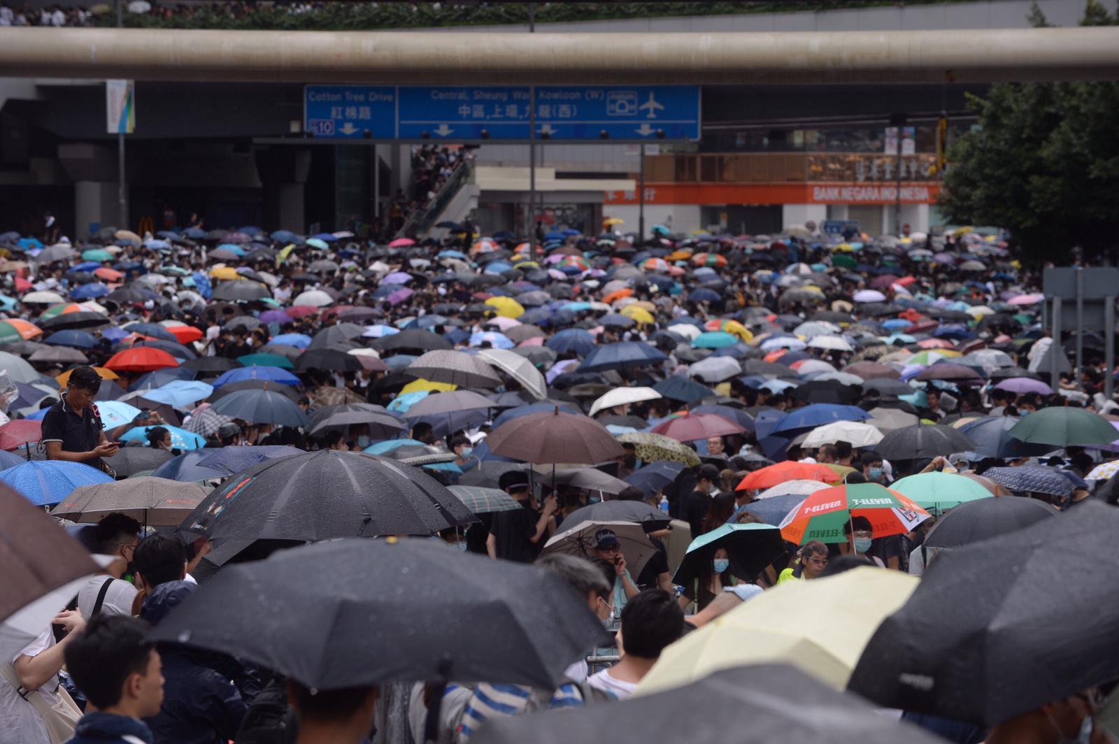 現場不時下驟雨,示威者手持雨傘,堅持留守現場。